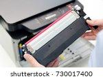 man replacing toner in laser... | Shutterstock . vector #730017400