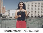 Small photo of TV reporter at work. Smiling journalist tells a report on a bridge in a big city on the background of houses