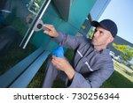 worker cleaning windows service ... | Shutterstock . vector #730256344