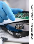 Small photo of A male repairman wearing blue gloves is holding a hard drive from computer or laptop in hands. Performs fault diagnostics and performs urgent repairs recovery of lost data during deletion HDD closeup