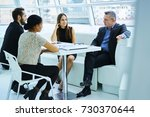 Small photo of Proud CEO explaining strategies for diversity crew of male and female employees during meeting table, partners discussing business ideas for startup project having conference in modern office