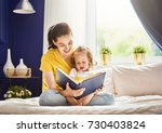 pretty young mother reading a... | Shutterstock . vector #730403824