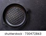 empty pan on a dark table  top... | Shutterstock . vector #730472863