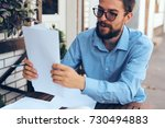 business man with glasses holds ... | Shutterstock . vector #730494883