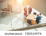 team sitting behind desk ... | Shutterstock . vector #730514974