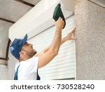 man installing roller shutter... | Shutterstock . vector #730528240