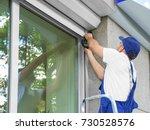 man installing roller shutter... | Shutterstock . vector #730528576