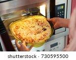 woman preparing pizza bought in ...   Shutterstock . vector #730595500