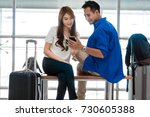 Small photo of Asian couple traveler using smartphone and listening the song when waiting the airplane arrive with luggage at the airport. Lover travel and transportation with technology concept.