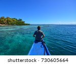 a man sitting on a wooden boat... | Shutterstock . vector #730605664