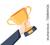 winning cup in hand. symbol of... | Shutterstock .eps vector #730804426