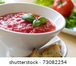 Bowl of tomato soup with bread crouton and basil - stock photo