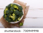 raw broccoli in a bowl on white ... | Shutterstock . vector #730949998