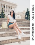 Small photo of Attractive carefree gorgeous mixed-race lady with bronze skin is on stroll, in jeans short shorts, so fit and slim body, chilling with hot tea, on concrete rung, writing message on her pda, sunny day
