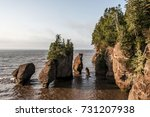 Small photo of Sunrise at famous Hopewell Rocks geologigal formations at low tide biggest tidal wave Fundy Bay New Brunswick Canada