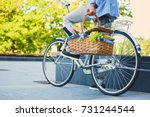 a man on a city bicycle holds... | Shutterstock . vector #731244544