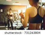 asian woman lifting dumbbell in ... | Shutterstock . vector #731263804