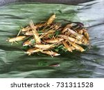 Small photo of Fried grasshoppers on green banana leaf.Crispiness or crispness is the gustatory sensation of brittleness in the mouth, such that the food item shatters immediately upon mastication. street food.