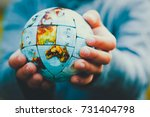 small hands holding the world... | Shutterstock . vector #731404798