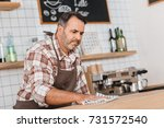 concentrated mature bartender... | Shutterstock . vector #731572540