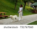 Stock photo pretty young african lady in white clothes walking with dog labrador in park in the morning 731767060