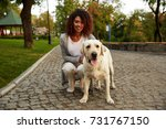 Stock photo portrait of young smiling african lady in casual clothes sitting near dog while walking in park 731767150