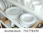 Small photo of Different plates on shelf of storage stand