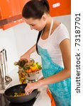 Beautiful young woman cooking in the kitchen - stock photo