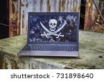 "Small photo of Laptop with a picture of a pirate flag ""Jolly Roger"" on the screen with rusty industrial destructed stuff on background"