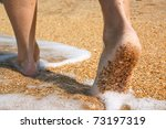 Barefoot feet walking in surf on sand coast - stock photo