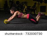Small photo of Young woman training with abs wheel roller