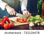 the chef in black apron cuts... | Shutterstock . vector #732126478