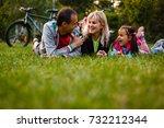 family lying on grass lying in... | Shutterstock . vector #732212344