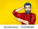 Stock photo pop art man with shocked facial expression surprised male in comic style showing by finger 732348400