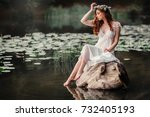 Small photo of Beautiful red haired girl in white vintage dress and wreath of flowers sitting on a snag in the middle of lake. Fairytale story. Warm art work.