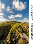 Small photo of Stumble head lighthouse on a sunny day with bridge and steps. Pencaer, Pembrokeshire, Wales, United Kingdom.