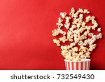 Paper cup with popcorn on color ...