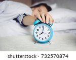 Small photo of Wake up in the morning, Defocus Woman sleep on bedroom, Time 8 o clock am, sleepy and lazy dont want getting out of bed. Girl catch and stop snooze alarm by hand