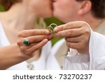 Bride and groom are holding wedding rings in theirs fingers and kissing - stock photo