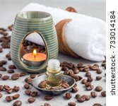 Small photo of Aroma lamp with coffee essential oil on woven mat, spa background, square format
