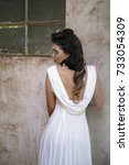 Small photo of Portrait of beautiful brunette woman with fantasy makeup wearing a white cowl back dress, leaning against a rustic warehouse wall with a window.