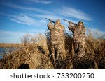 Two camouflaged waterfowl hunters shooting into sky during duck hunting on sunny day