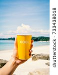 female hand holding yellow cup...   Shutterstock . vector #733438018