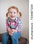 Small photo of Red-haired girl with dental caries is sitting on a suitcase