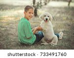 Small photo of Retriever pup Lovely scene handsome teen boy enjoying summer time vacation with best friend dog ivory white labrador puppy.Happy airily careless childhood life in world of dreams.