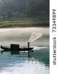 A fisherman casting his net from the boat on the river - stock photo