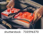Small photo of A car mechanic replaces a battery