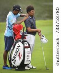 Small photo of KUALA LUMPUR, MALAYSIA - OCTOBER 13, 2017 : Nicholas Fung of Malaysia (R) receives a shoulder massage by his caddie on the fairway during 2017 CIMB Classic golf tournament in Kuala Lumpur