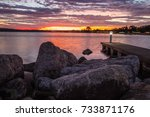 Small photo of Downtown Traverse City Coastal Sunrise. Morning sunrise over the rocky coast of Grand Traverse Bay with downtown Traverse City, Michigan in the background.