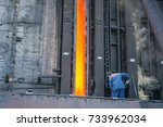 Small photo of Coke furnace. Production of coke. Steel works. The person loads coke in the furnace. The heated coal. NLMK.